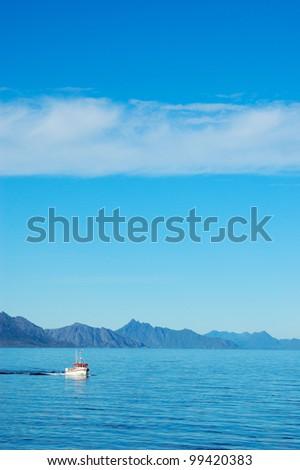 Lonely fishing boat near Moskenes, Lofoten in summer 2006. - stock photo