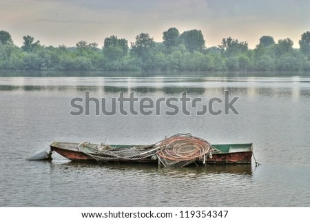 Lonely fishing boat on Danube - stock photo