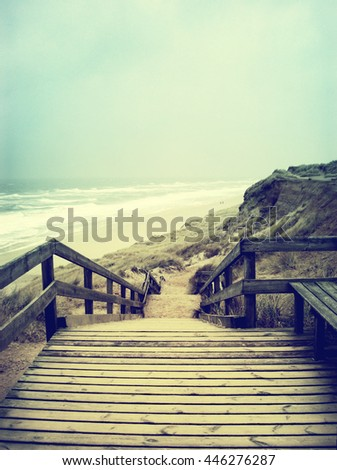 Lonely footpath or wooden stairway through a beach dune. Beach on Sylt with stormy sky - stock photo