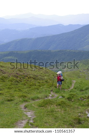 Lonely girl climbs into the mountains along the path, her backpack and it is based on trekking sticks - all against the backdrop of green mountains - stock photo
