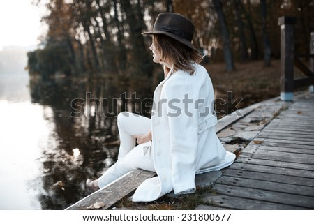 Lonely girl in cloudy weather sits near the water and looks into the distance - stock photo