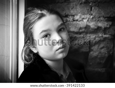 Lonely girl near window thinking about something. Black and white photo - stock photo