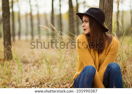 Lonely girl sitting in the autumn forest - stock photo
