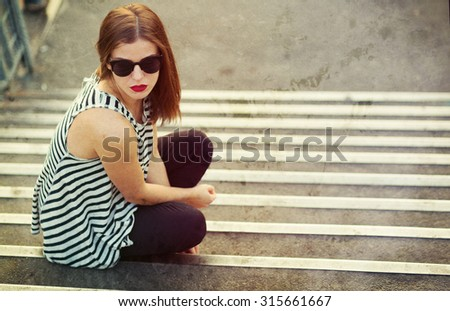Lonely girl sitting on the stairs. Toned and textured image - stock photo