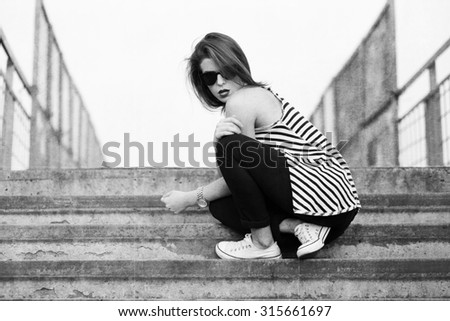 Lonely girl standing on the stairs. Black and white textured image - stock photo