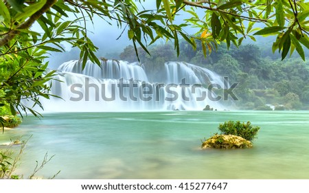 Lonely island the Ban Gioc waterfall with velvety water flow down river side fluted foliage foreground of misty air of the morning calm as a picture wearing on earth - stock photo
