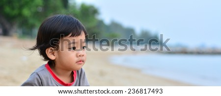 lonely little boy with sad face closeup at beach - stock photo