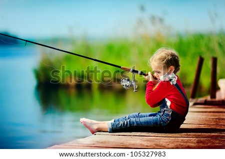 lonely little child fishing from wooden dock on lake - stock photo