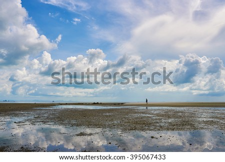 Lonely man figure and clouds reflecting in the sea - stock photo