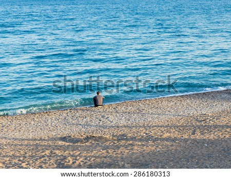 lonely man on the beach - stock photo