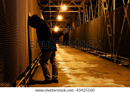 Lonely man resting on bridge - stock photo