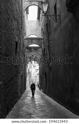 Lonely man walking down the alleys of Siena. - stock photo