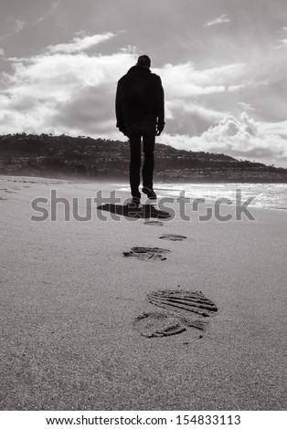 Lonely man walking on a beach (black and white) - stock photo