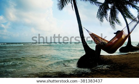 Lonely man watching the sunset sitting in a hammock on the beach - stock photo