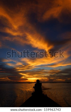 Lonely men silhouettes on sunset sky beautiful lagoon - stock photo