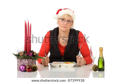 Lonely middle aged caucasian woman with Santa hat, sitting at table with microwave food. Sad Christmas dinner. Studio shot. White background. - stock photo