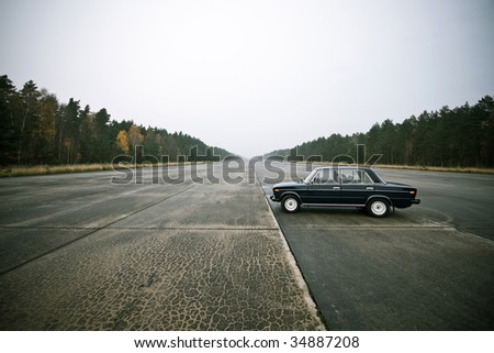 lonely old car on an airstrip - stock photo