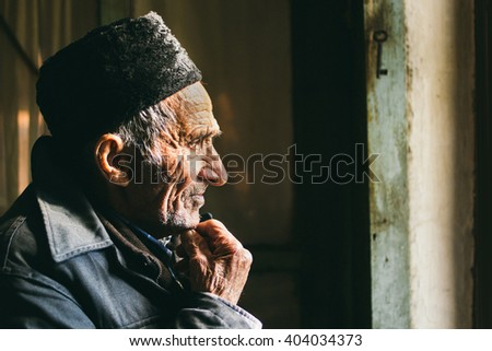Lonely old man in an old-age home staring out of a window as he longs for his freedom and friends  - stock photo