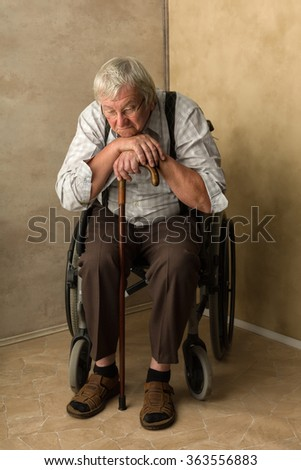 Lonely old man in nursing home leaning on his cane - stock photo