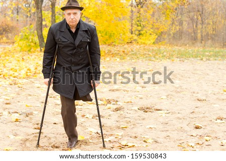 Lonely one-legged senior Caucasian man walking with crutches in an Autumn day in the park, with withered foliage in the background - stock photo