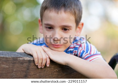 lonely orphan in park crying - stock photo