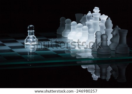 lonely pawn against the entire set of opponent's pieces. Only the center illuminated  - stock photo