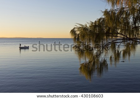 Lonely person fishing at sunrise on a very calm day - stock photo