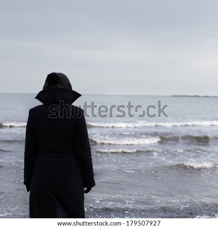 Lonely person on a beach in winter time - stock photo