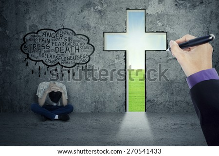 Lonely person thinking his problem while sitting near a cross - stock photo