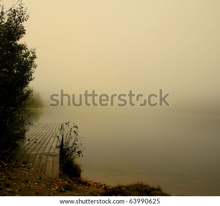 Lonely pier on the foggy lake - stock photo