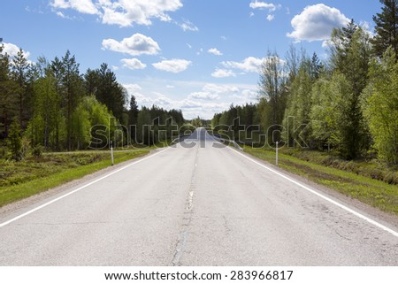 Lonely road in Finland. Dry asphalt road in a sunny day. Clouds are in the sky. - stock photo