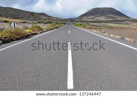 Lonely road in the deseret  on a cloudy sky - stock photo