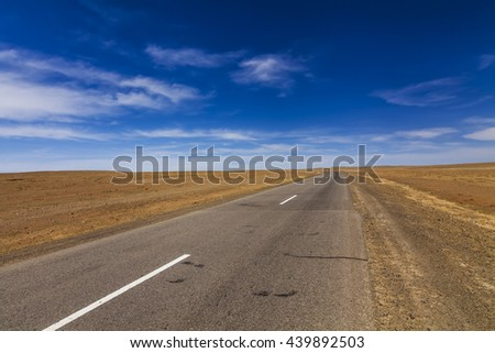 Lonely road in the desert under a blue sky. - stock photo