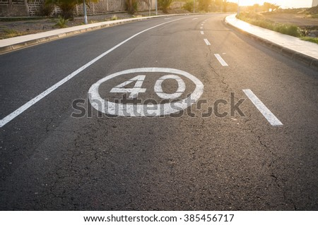 Lonely road is coated with asphalt on a speed limit sign - stock photo