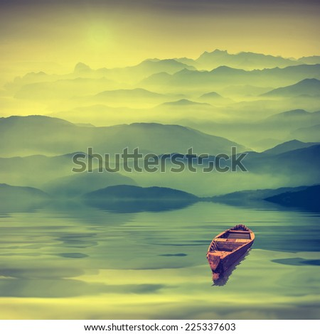 Lonely rustic boat on a high mountain lake in foggy valley - stock photo