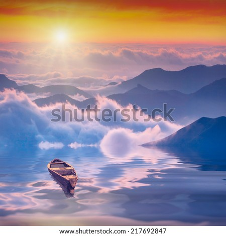 Lonely rustic boat on a high mountain lake in foggy valley of Crimea, Ukraine - stock photo