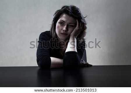 Lonely sad girl in black sitting at the table - stock photo