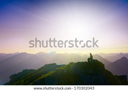 lonely sad girl sitting on mountain summit looking over alps - stock photo