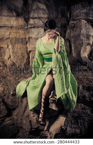 Lonely sad princess is sitting on the rock.  - stock photo