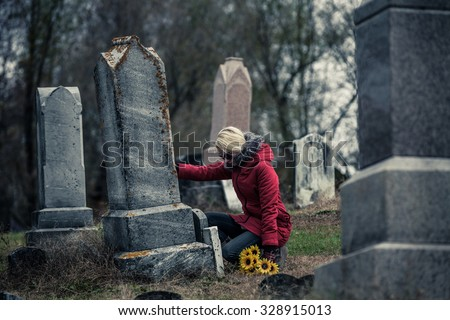 Lonely Sad Young Woman in Mourning with Sunflowers Touching a loved one's Gravestone in a Cemetery - stock photo