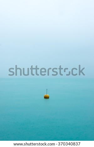 Lonely sea buoy in fog. Buoy in sea mist. Sea buoy in a foggy sea. Buoy background. Blue sea in fog. Tranquil sea. Calm sea with buoy. Tranquil sea background. Endless sea. Sea water. Turquoise sea. - stock photo
