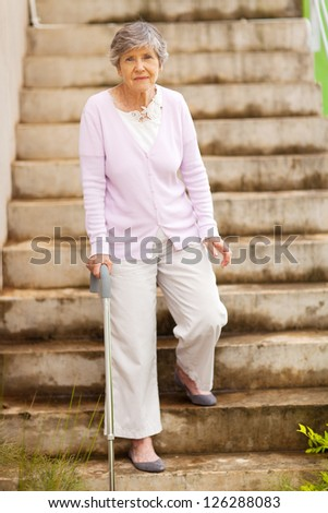 lonely senior woman standing by stairway - stock photo