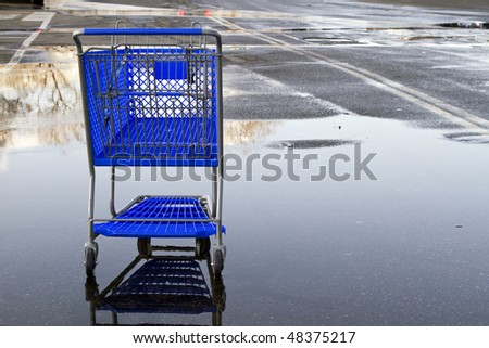 Lonely shopping cart on the empty parking lot with reflection. - stock photo