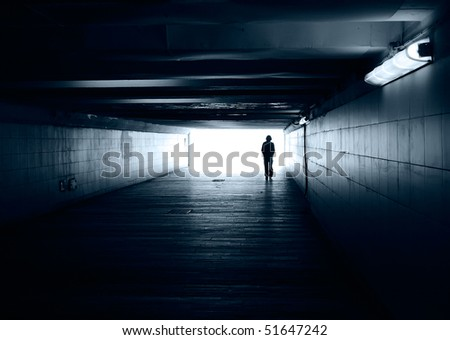 Lonely silhouette in a subway tunnel - stock photo