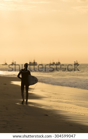 Lonely silhouette of surfer holding his board and walking on the beach of Mancora with an orange yellow sunset and the harbor in the background. Peru 2015. - stock photo