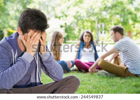 Lonely student feeling excluded on campus at the university - stock photo