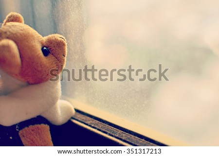 Lonely Teddy bear looking out the window. Concept of Nostalgia. Toned image. - stock photo
