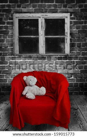 lonely teddybear sitting on a red chair - stock photo