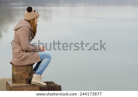 Lonely teenage girl sitting on the dock on cold winter day. - stock photo