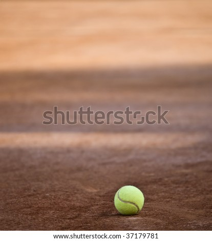Lonely tennis ball on a tennis clay courts - stock photo